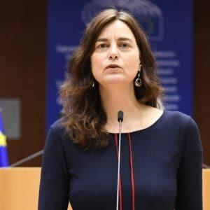 Alexandra Geese nella sala plenaria al banco dei relatori. Sullo sfondo 2 bandiere dell'UE.